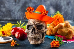 Mexican dia de los muertos Day of the Dead background. Skull in a traditional sombrero hat, yellow and orange cempasuchil flowers or marygold and pan de muertos. Traditional festive altar offering