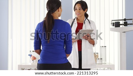Mexican doctor talking to African American patient using pad