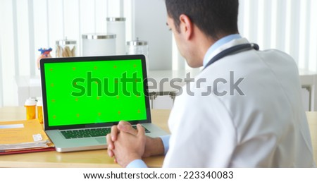 Mexican doctor talking to laptop with green screen