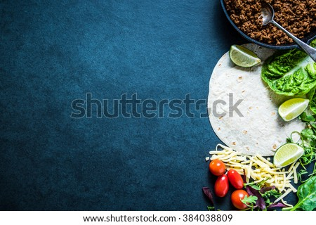 Mexican fajitas or tortillas, food border background with space for text or recipe. Overhead on dark slate. #384038809
