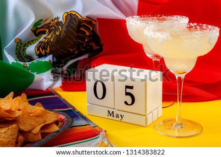 Mexican fiesta and Cinco de Mayo party concept theme with block calendar set on May 5th, traditional rug or serape, two margaritas, bowl of tortilla chips and the flag of mexico #1314383822