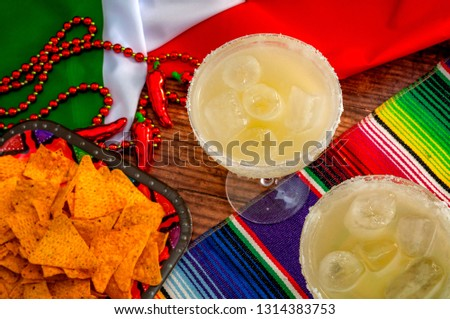 Mexican fiesta and Cinco de Mayo party concept theme with jalapeno pepper beads necklace, traditional rug or serape, two margarita glasses, chips and the flag of Mexico #1314383753