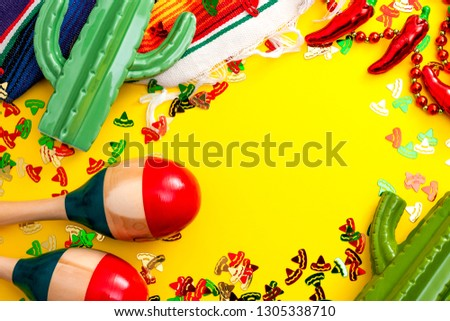 Mexican fiesta and Cinco de Mayo party concept theme with jalapeno pepper necklace, maracas, cactus and traditional rug covered in sombrero shaped confetti on yellow background with copy space #1305338710