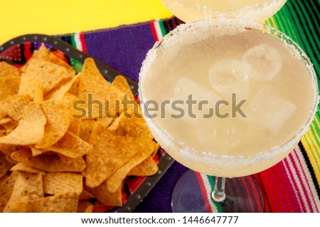 Mexican fiesta and Cinco de Mayo party concept theme with traditional table runner or serape, two glasses of margarita on the rocks  and tortilla chips on a yellow background #1446647777
