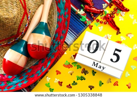 Mexican fiesta and Cinco de Mayo party concept with calendar set on May 5th, jalapeno pepper necklace, maracas, cactus and traditional rug covered in sombrero shaped confetti on yellow background #1305338848