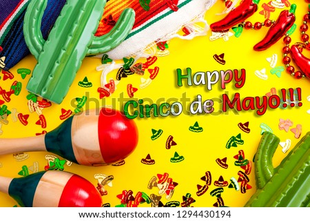 Mexican fiesta and latino party concept theme with jalapeno pepper necklace, maracas, cactus and traditional rug covered in sombrero shaped confetti on yellow background with Happy Cinco de Mayo text #1294430194