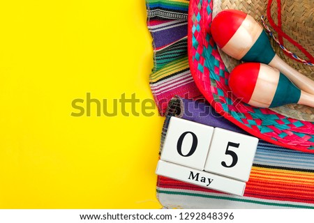 Mexican fiesta poster and Cinco de Mayo party concept theme with calendar on may 5th, red and blue maracas, sombrero and traditional rug on yellow background with copy space #1292848396