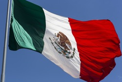 Mexican Flag flying in a blue sky in high resolution