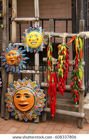 Mexican folk art of hand painted clay masks of Aztec sun and chili ristras.