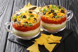 Mexican food authentic seven-layer dip salad of bean paste, guacamole, sour cream and salsa close-up on the table. horizontal