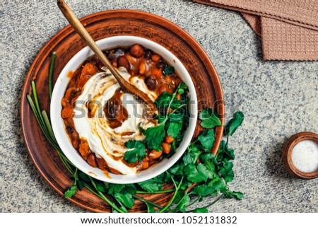 Mexican food. Beans. A bowl of red bean chili with coriander and cream, top view, gray stone background