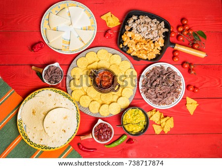 Mexican food concept: tortilla chips, guacamole, salsa, chilli, beans, pulled beef, chicken, cheese and fresh ingredients over vintage red rustic wooden background. Top view #738717874