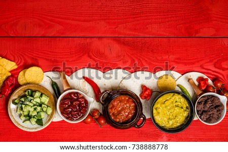 Mexican food concept: tortilla chips, guacamole, salsa, chilli, refried black beans, and fresh ingredients over vintage red rustic wooden background. vegetarian. Top view #738888778