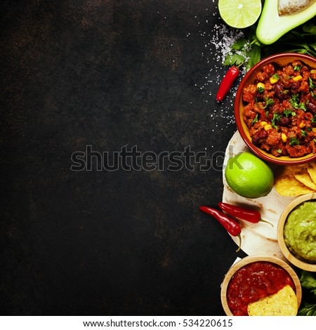 Mexican food concept: tortilla chips, guacamole, salsa, chilli with beans and fresh ingredients over vintage rusty metal background. Top view #534220615