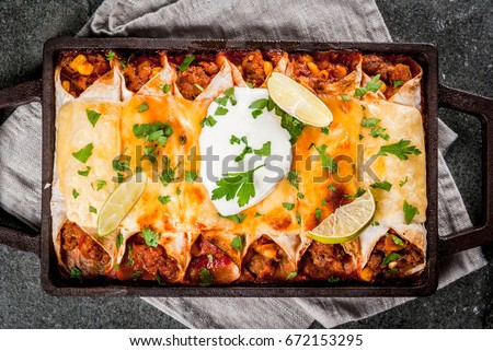 Mexican food. Cuisine of South America. Traditional dish of spicy beef enchiladas with corn, beans, tomato. On a baking tray, on a black stone background. Top view