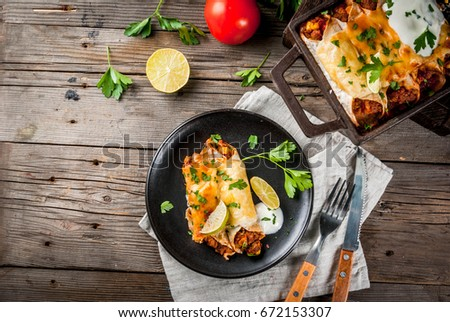 Mexican food. Cuisine of South America. Traditional dish of spicy beef enchiladas with corn, beans, tomato. On a baking tray, on old rustic wooden background. Copy space top view.