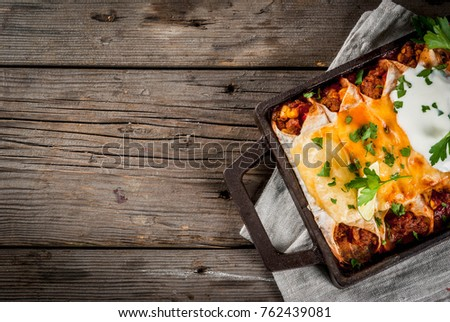 Mexican food. Cuisine of South America. Traditional dish of spicy beef enchiladas with corn, beans, tomato. On a baking tray, on old rustic wooden background. Top view copy space