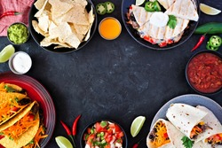 Mexican food frame, above view over a dark slate background. Tacos, nachos, quesadilla and burritos. Copy space.