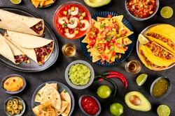 Mexican food, many dishes of the cuisine of Mexico, flat lay, shot from above on a black background. Nachos, tequila, guacamole etc