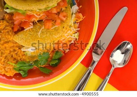 Mexican food plaate with tacos, bean and rice on brightly colored plate with flatware- silverware