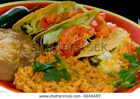 Mexican food plate with tacos, bean and rice on brightly colored plate