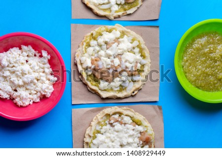 Mexican food: sopes with green sauce, fresh cheese and beans on blue background
