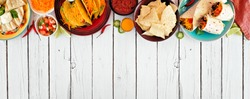 Mexican food top border, Overhead view on a white wood banner background. Quesadilla, tacos, nachos and burritos. Copy space.