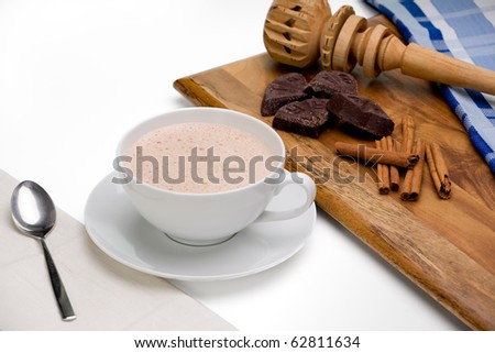 Mexican hot chocolate with chocolate, cinnamon, and stirrer on wooden board.