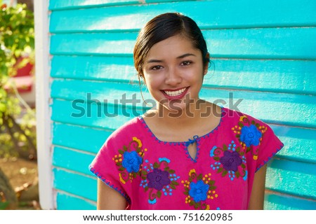 Mexican latin woman with mayan dress smiling in turquoise wall #751620985