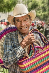 Mexican man selling bags An old man working as a handmade bag vendor