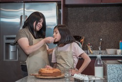 Mexican mother and daughter eating  home made bread in the kitchen