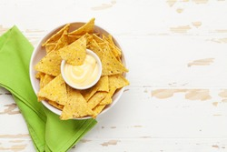 Mexican nachos chips with cheese sauce. Top view flat lay on wooden table with copy space