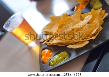 Mexican nachos dish with guacamole sauce and cheese sauce. With accompaniment of beer and chips. #1258646998