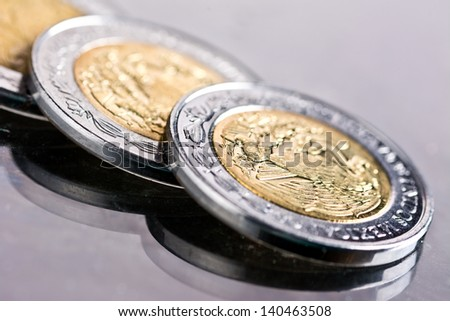 Mexican Pesos Coins on a Shiny Black Floor Background