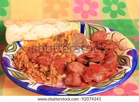Mexican plate with Chorizo, rice, and refried beans on brightly colored background.