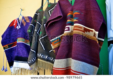 Mexican ponchos hanging for sale