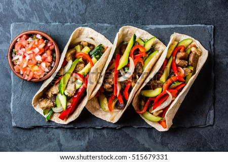 Mexican pork tacos with vegetables and salsa. Tacos al pastor on black stone slate plate on black background. Top view