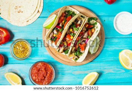 Mexican pork tacos with vegetables on wooden blue rustic background. Top view