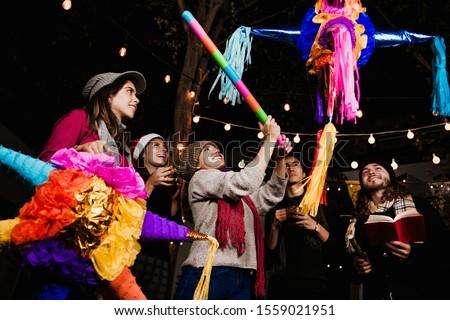 Mexican Posada friends breaking a Piñata celebrating Christmas Mexico