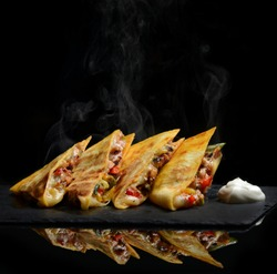 Mexican Quesadilla wrap with chicken   sweet pepper sour cream and salsa hot with steam smoke on black background