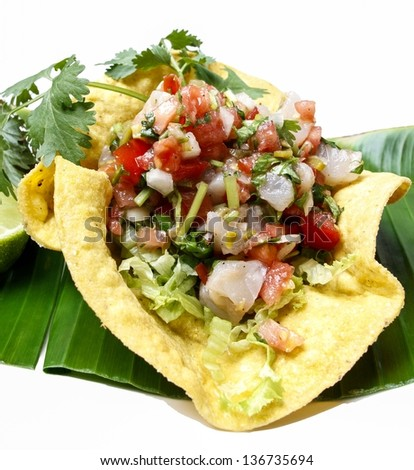 Mexican salad in a tortilla on banana leaf, isolated on white background