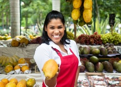 Mexican saleswoman offering fruits on a farmers market