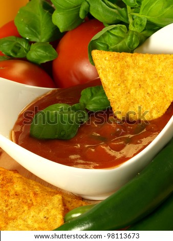 Mexican snack with golden nachos and hot salsa sauce