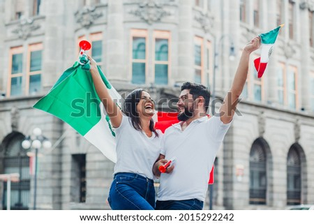Mexican soccer fans holding flags and trumpets to celebrate in Mexico City