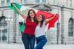 Mexican soccer fans with mexican flag outdoors in Mexico