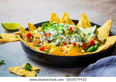 Mexican street corn salad with cheese and nachos chips in a black platter. Mexican food concept. Foto stock ©