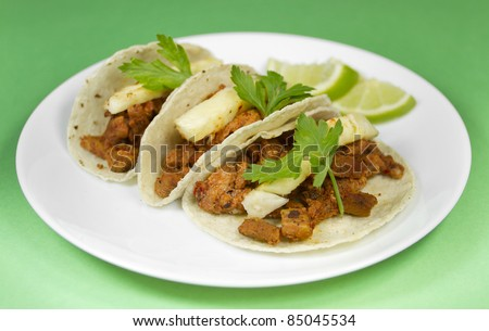 "Mexican Tacos Al Pastor made with pork meat and seasoned with dried chili and adorned with pineapple slices and parsley. They are known in spanish as ""Tacos Al Pastor""."