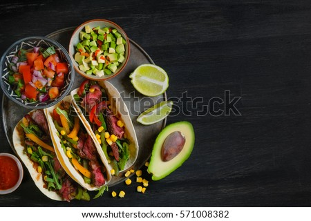 Mexican tacos - traditional dish with ingredients meat and vegetables on the plate on a black wooden background, top view. Black background for text and design. Flat top view. #571008382