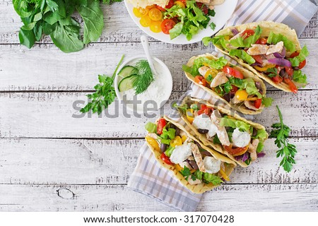 Mexican tacos with chicken, bell peppers, black beans and fresh vegetables and tartar sauce. Top view #317070428