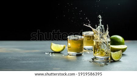 Mexican tequila with lime and salt on stone background. concept luxury drink. Alcoholic drink. Freeze motion, drops in liquid splash Mexican national drink. space for text. Foto stock ©